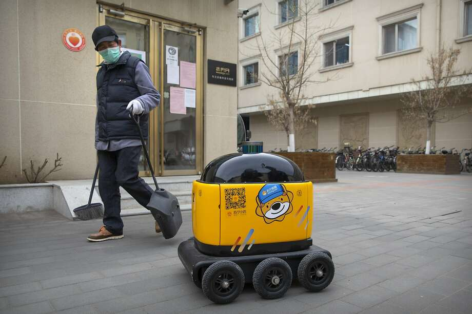 A maintenance worker looks at a robot outside the offices of ZhenRobotics in Beijing. Photo: Photos By Mark Schiefelbein / Associated Press