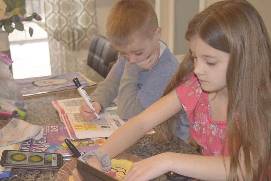 Teagan Cantrell (right), 8, and Nash Cantrell, 4, work on projects Wednesday while home from school after the state closed all schools amid concerns about the COVID-19 coronavirus.