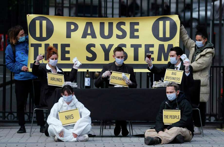 Members of the group 'Pause the System' protest in front of the entrance to Downing Street in London, Friday, March 20, 2020. For most people, the new coronavirus causes only mild or moderate symptoms, such as fever and cough. For some, especially older adults and people with existing health problems, it can cause more severe illness, including pneumonia. Photo: Frank Augstein, AP / Copyright 2020 The Associated Press. All rights reserved