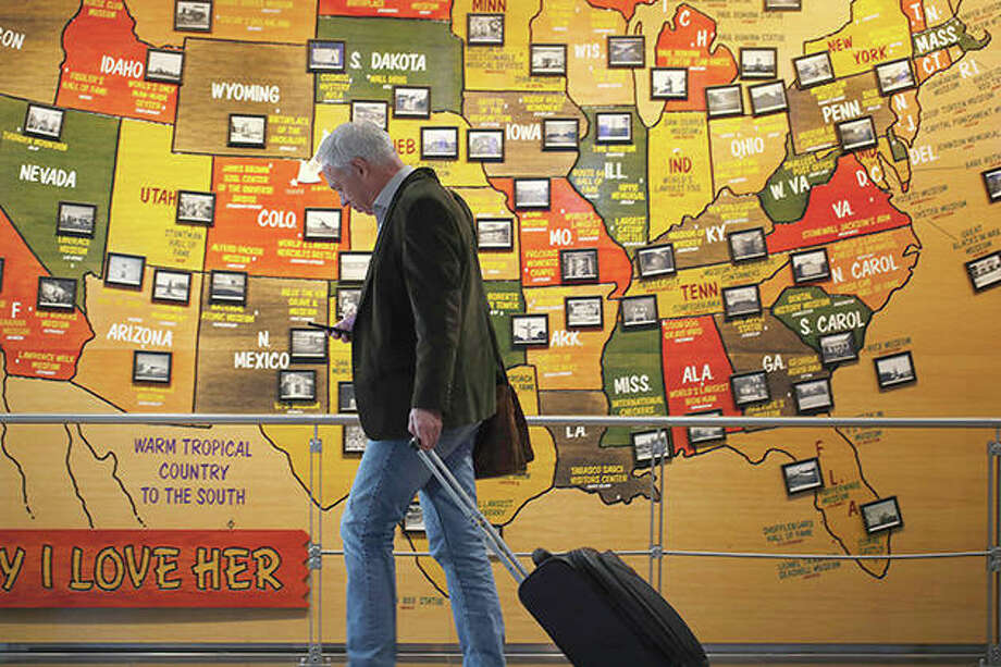 A traveler checks his phone while passing a map of the United States on the way to an airport security checkpoint. Americans increasingly are worried they or a loved one will be infected by the coronavirus, with two-thirds now saying they're at least somewhat concerned — up from less than half who said so a month ago. That's according to a new poll from The Associated Press-NORC Center for Public Affairs Research that finds about three in 10 Americans say they're not worried at all. Photo: David Zalubowski | AP