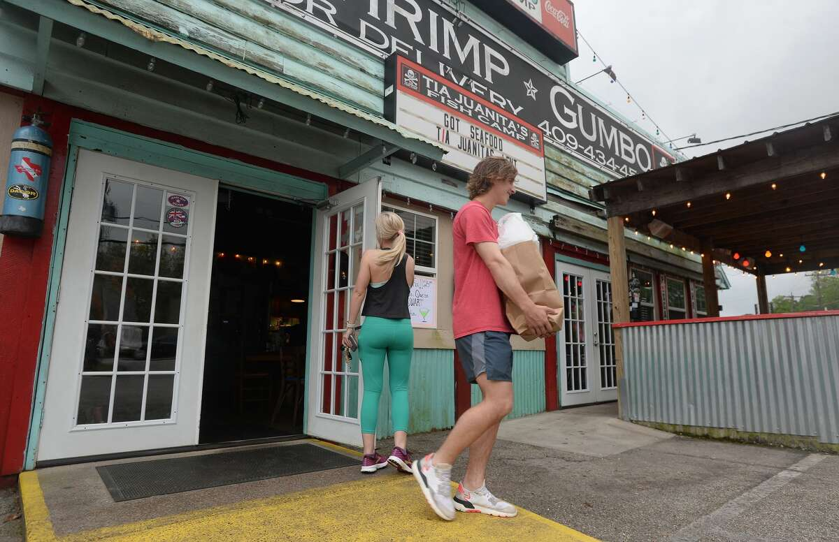 Maddie Allen holds the door for Tripp Daleo as they and Katherine McAlee (not pictured) carry out their to-go order at the Tia Juanita's Fish Camp in Beaumont on the first day of area restaurant and bar closures. Photo taken Thursday, March 19, 2020 Kim Brent/The Enterprise