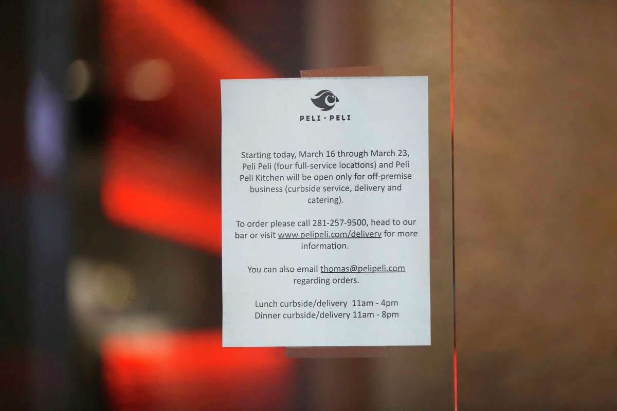 """A sign telling customers that Peli Peli is only open for off-premise business, which includes curbside service, delivery and catering, in the Galleria, in Houston,Monday, March 16, 2020. Peli Peli announced they were offering """"curbside"""" lunches for patrons."""