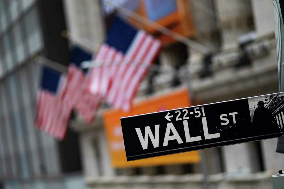 FILE - This Jan. 31, 2020, file photo shows a Wall Street sign in front of the New York Stock Exchange.  Global stock markets and U.S. futures are up on hopes that government aid and central banks can shield the global economy against the rising impact of the coronavirus pandemic. Indexes in London, Frankfurt, Shanghai and Hong Kong advanced Friday, March 20, 2020 and U.S. futures were also higher. Photo: Mark Lennihan, AP / Copyright 2020 The Associated Press. All rights reserved