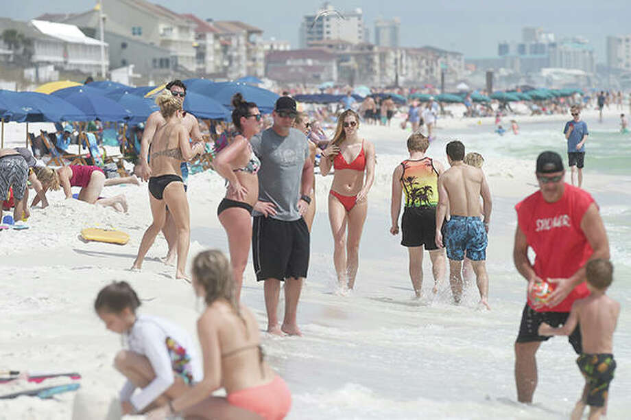 "Beachgoers enjoy a sunny day Wednesday in Destin, Florida. There's a new type of social policing out there that's developed almost as quickly as the viral disease that spurred its arrival. It's called ""quarantine shaming,"" calling out those who are leaving the house for daily activities or who aren't abiding by social distancing rules. And it's part of a new reality for Americans who must navigate a world of rapidly evolving social norms in the age of COVID-19. Photo: Devon Ravine 