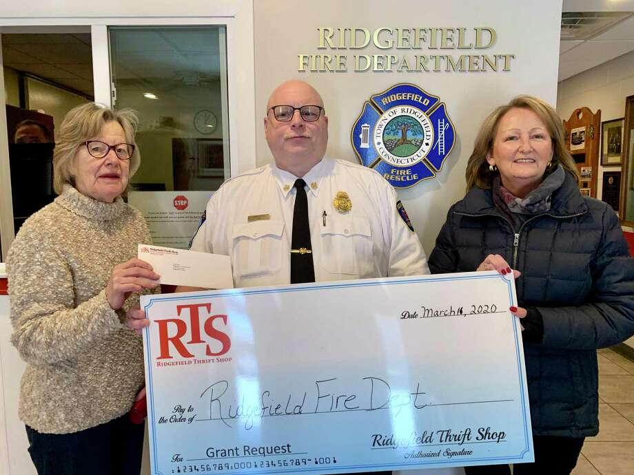 Ridgefield Thrift Shop volunteer Marilyn Maneri; Ridgefield Fire Chief Jerry Myers and RTS volunteer Mary Coleman hold a grant check for the Ridgefield Fire Department. Photo: Contributed Photo