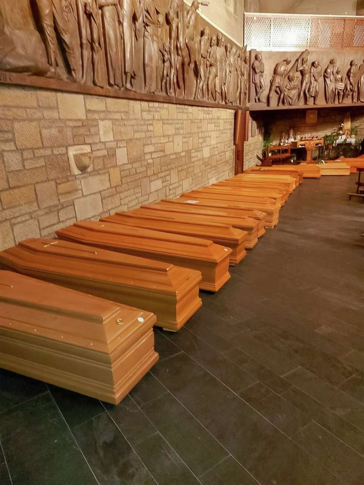 This photo provided by Italian news agency ANSA on March 19, 2020 shows coffins aligned in a chapel in Bergamo, Lombardy on March 18, 2020 prior to being transported for cremation.