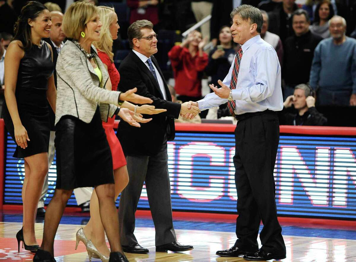 UConn coach Geno Auriemma, left, greets DePaul coach Doug Bruno before a December 2014 game in Bridgeport.