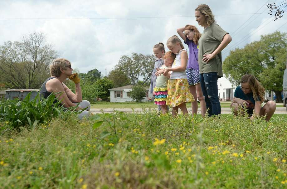 Cynthia Peveto talks with Ashley Behn and her children as they stop to chat while Peveto weeds a garden at the First Baptist Church in Nome, where Behn's husband is the pastor. Photo taken Thursday, March 19, 2020 Kim Brent/The Enterprise Photo: Kim Brent/The Enterprise