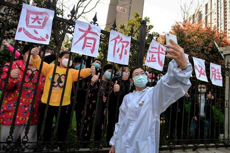 """This photo taken on March 18, 2020 shows a member of a medical assistance team from Yunnan province taking a selfie with Wuhan residents who set up banners of appreciation as the team depart after helping with the COVID-19 coronavirus recovery effort in Wuhan, in China's central Hubei province. - Medical teams from across China began leaving Wuhan this week after the number of new coronavirus infections dropped. The full banner reads """"Appreciate having you. Wuhan will win!"""" (Photo by STR / AFP) / China OUT (Photo by STR/AFP via Getty Images)"""