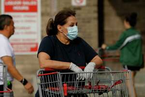 A woman wears a face mask and gloves as she waits to enter the Costco Wholesale at Bunker Hill Road on Friday, March 13, 2020, in Houston. People are rushing to grocery stores amid fears of the new coronavirus pandemic.