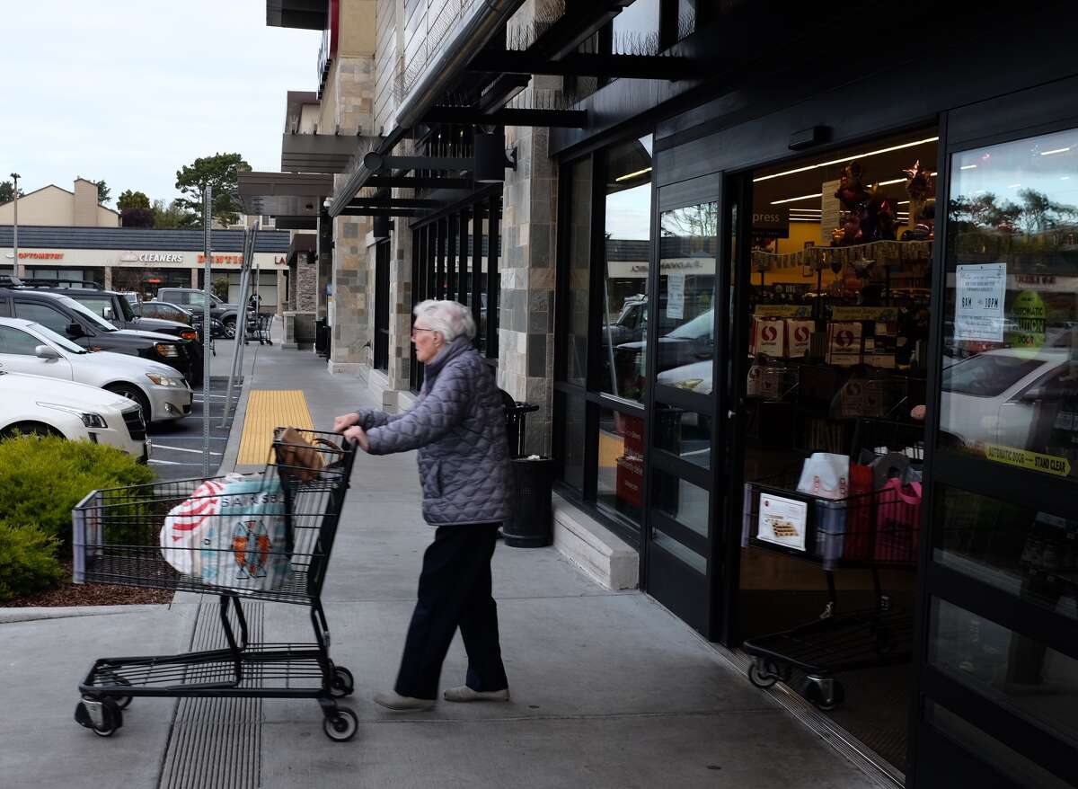 A shopper leaves the Safeway in the Fairmont Shopping Center in Pacifica during seniors-only hours Thursday, March 19, 2020.