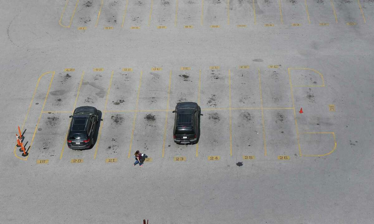 A woman walks to one of two parked cars in an otherwise empty parking lot at Franklin and La Branch Streets on March 17, 2020, in Houston. The city is seeing less traffic because of the Coronavirus outbreak.