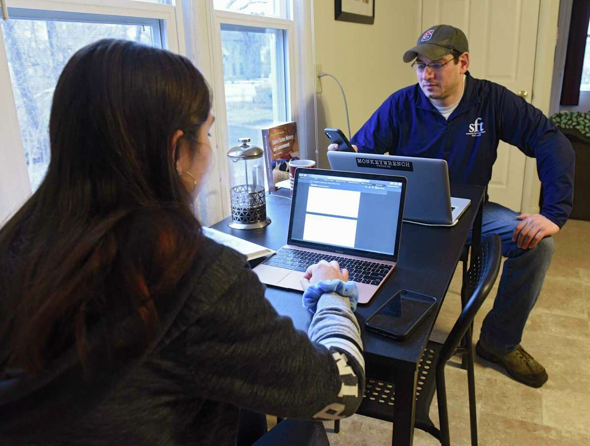 Schenectady High School U.S. history teacher Mike Silvestri calls his students who he sees are not logged on to Google classroom at his home on Friday, March 20, 2020 in Rensselaer, N.Y. Silvestri's 14-year-old daughter Zoe, a freshman at Albany High School, is seen working on a paper for school. (Lori Van Buren/Times Union)