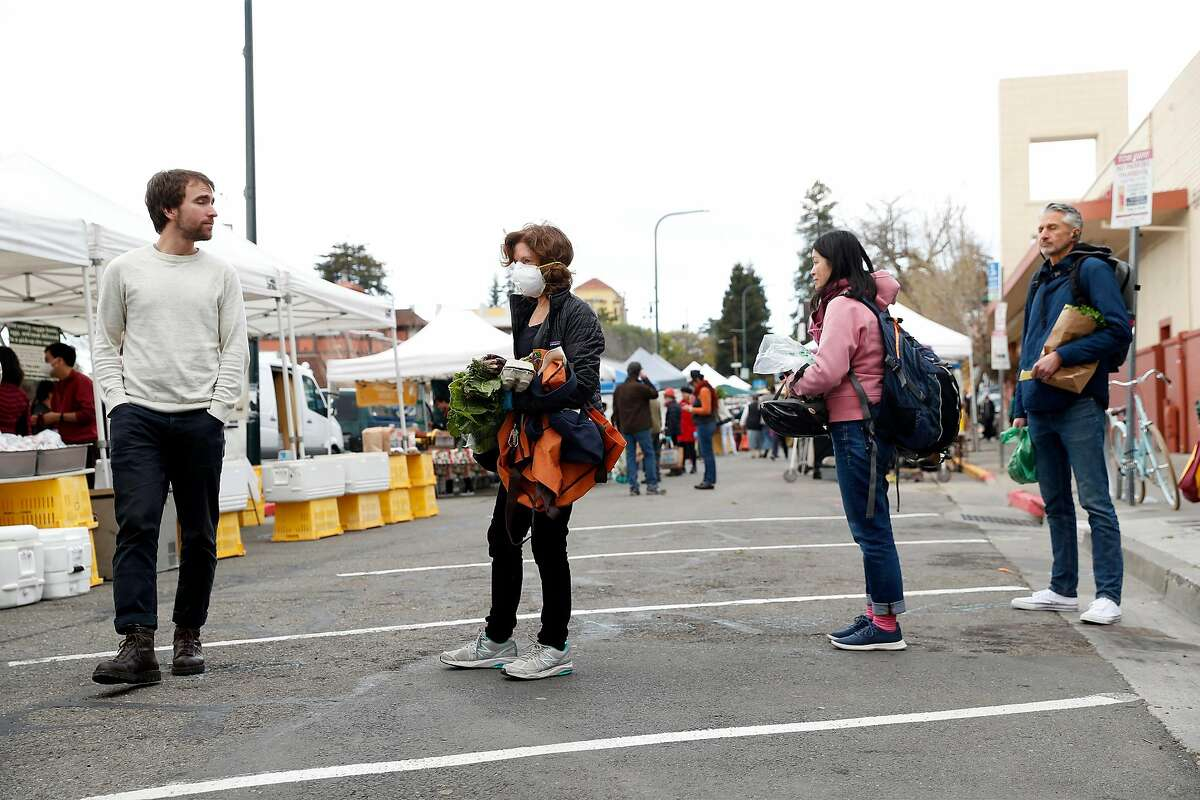 Shoppers adhere to social distancing guidelines while waiting in line at the Berkeley Farmers Market on Shattuck Avenue in Berkeley, Calif., on Wednesday, March 19, 2020.