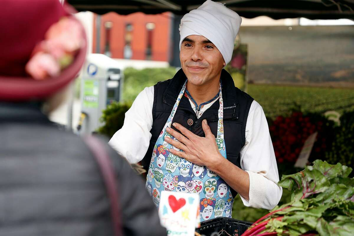 Green Thumb Organics' Efrain Jimenez thanks a customer for a purchase at the Berkeley Farmers Market on Shattuck Avenue in Berkeley, Calif., on Wednesday, March 19, 2020.