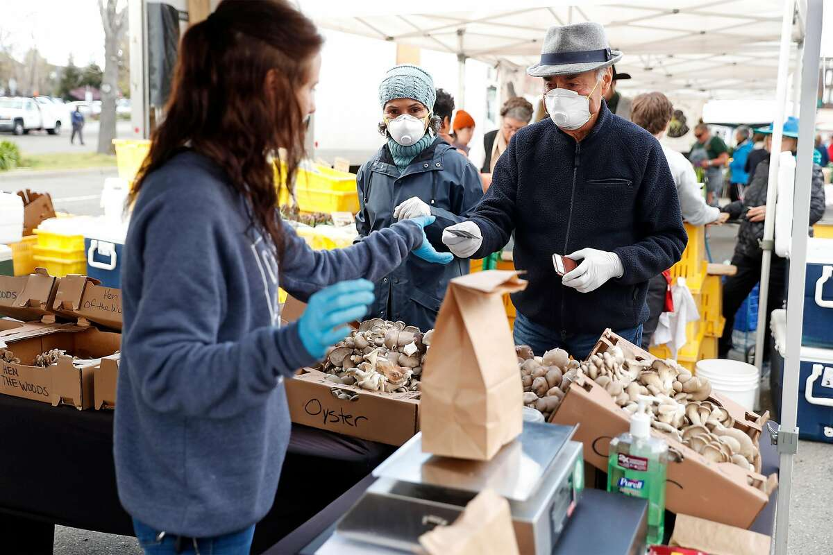 Lyla Moaven and Mansor Shokohi buy mushrooms from E&H Farms' Thea Tull at the Berkeley Farmers Market on Shattuck Avenue in Berkeley, Calif., on Wednesday, March 19, 2020.