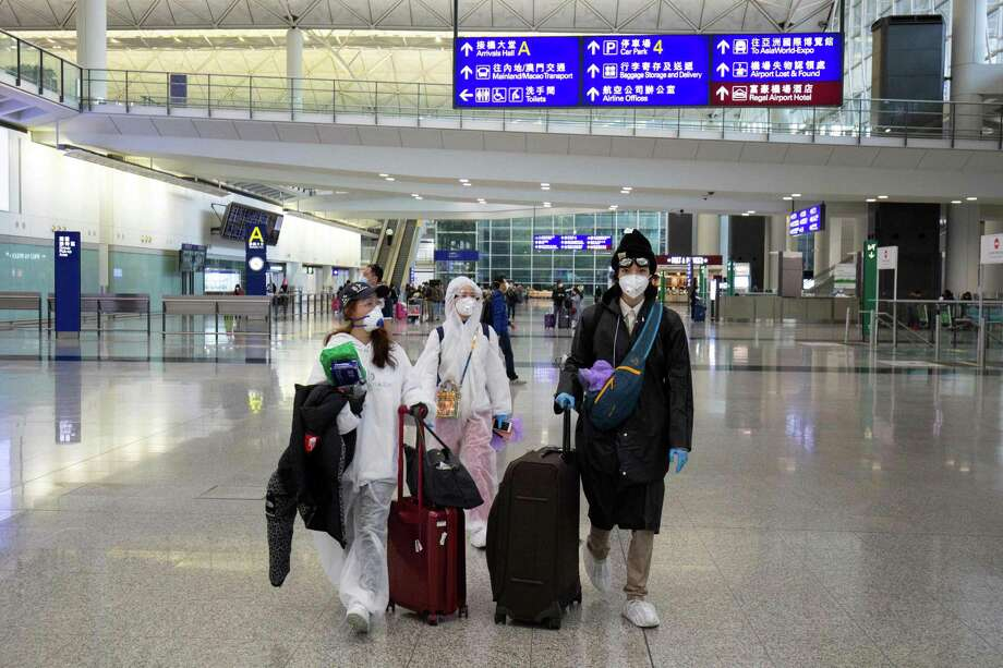 Passengers wearing protective gear as a precautionary measure against the COVID-19 coronavirus walk in the arrivals area after landing at the Hong Kong International Airport in Hong Kong last week. Photo: Getty Images / AFP or licensors