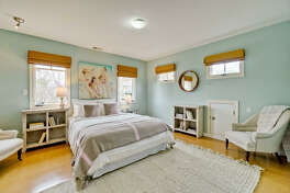 Picture and clerestory windows welcome natural light into this bedroom.