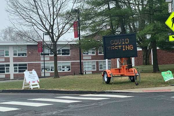 The parking area outside Saxe Middle School was the scene of the first COVID-19 testing for the disease in New Canaan recently. Eight New Canaan residents have died from the coronavirus. The virus causes COVID-19.