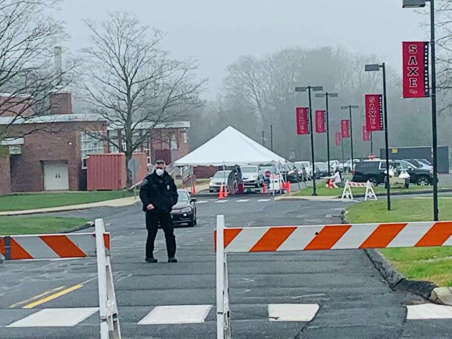 Cars line up for drive-thru testing for the disease COVID-19 recently while New Canaan Police barricade the South Avenue entrance to Saxe Middle School. COVID-19 is caused by the coronavirus. The death toll from the virus remained at 14 on Tuesday, April 14, 2020, days after fields, and parks closed for at least a month to stop its spread. Photo: John Kovach / Hearst Connecticut Media / New Canaan Advertiser