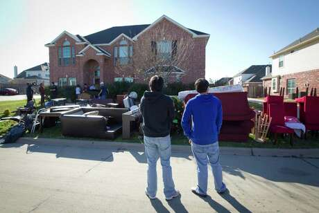 In this Dec. 27, 2011 photo, neighbors watch as all the possessions that squatters had moved into a home in Mansfield, Texas were carried to the curb. They were evicted in November. Nine people in Tarrant County have been indicted on charges related to unlawful trespassing or possession of vacant homes, the Fort Worth Star-Telegram reported. (AP Photo/Star-Telegram, Joyce Marshall)