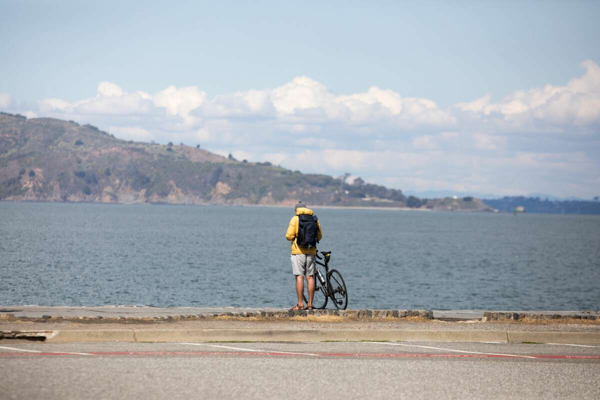 A bicyclist takes a break along Marina Green in San Francisco, Calif. on March 20, 2020. The Bay Area is under a shelter-in-place order due to the the COVID-19 coronavirus.