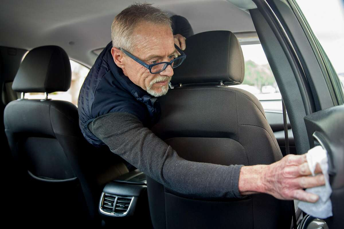 Lyft driver Steven Smith uses a sanitizing wipe to disinfect his vehicle as he waits to get a call from a passenger in San Francisco, Calif. Thursday, March 19, 2020. Smith and other Lyft drivers have seen a decline in ridership amidst the Bay Area's shelter-in-place in response to the global outbreak of the Coronavirus.
