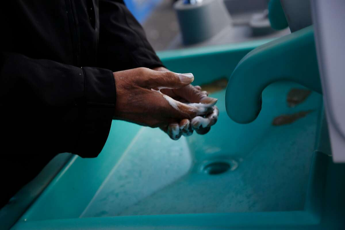 Hanna Wallace washes his hands at a hand washing station outside of Multi-Service Center South where he says he currently has a bed on Thursday, March 19, 2020 in San Francisco, Calif.