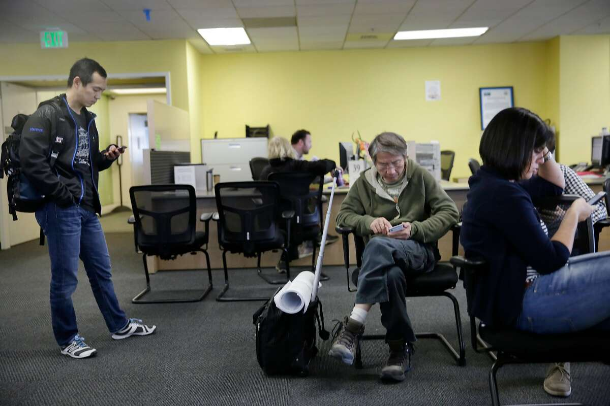 David Wang (l to r); Peter Fan, Anna Putnam and Daniel Gorham (partially seen behind Putnam) check their phones as they wait to apply for permits on the fifth floor at the Department of Building Inspection on Wednesday, November 18, 2015 in San Francisco, Calif.