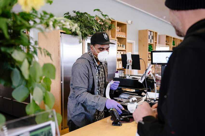 Sales associate Dustin Brown wears an N95 mask while ringing up customers at Harborside in Oakland, California, US, on Tuesday, March 17, 2020.