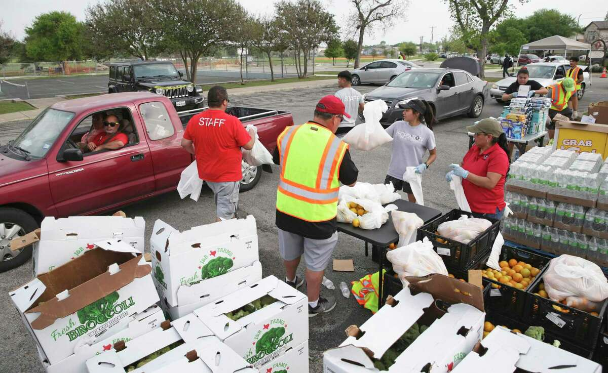 San Antonio Parks and Recreation personnel hand out food items provided by the San Antonio Food Bank for distribution to those in need at Gilbert Garza Park on March 19, 2020.