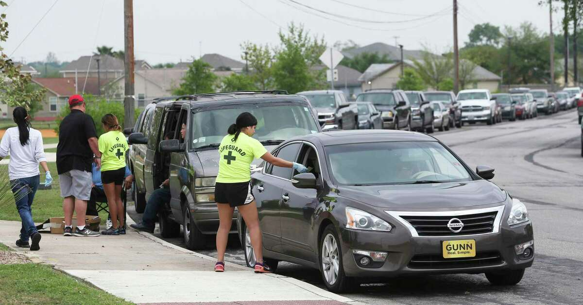 Workers preregister cars in a line stretching for blocks as San Antonio Parks and Recreation personnel hand out food items provided by the San Antonio Food Bank for distribution to those in need at Gilbert Garza Park on March 19, 2020.
