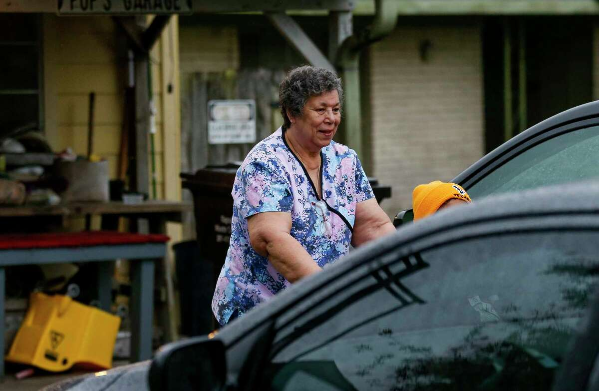 Mary Morris pushes one of her clients toward a taxi cab before going to a doctor's appointment Friday, March 20, 2020, in South Houston, Texas. More than a million sick and elderly Texans rely on home health attendants, like Morris. These caregivers are some of the most burdened in the health care industry; making little above minimum wage, often have multiple jobs, no paid sick leave, and are caring for the people most vulnerable to Covid-19.