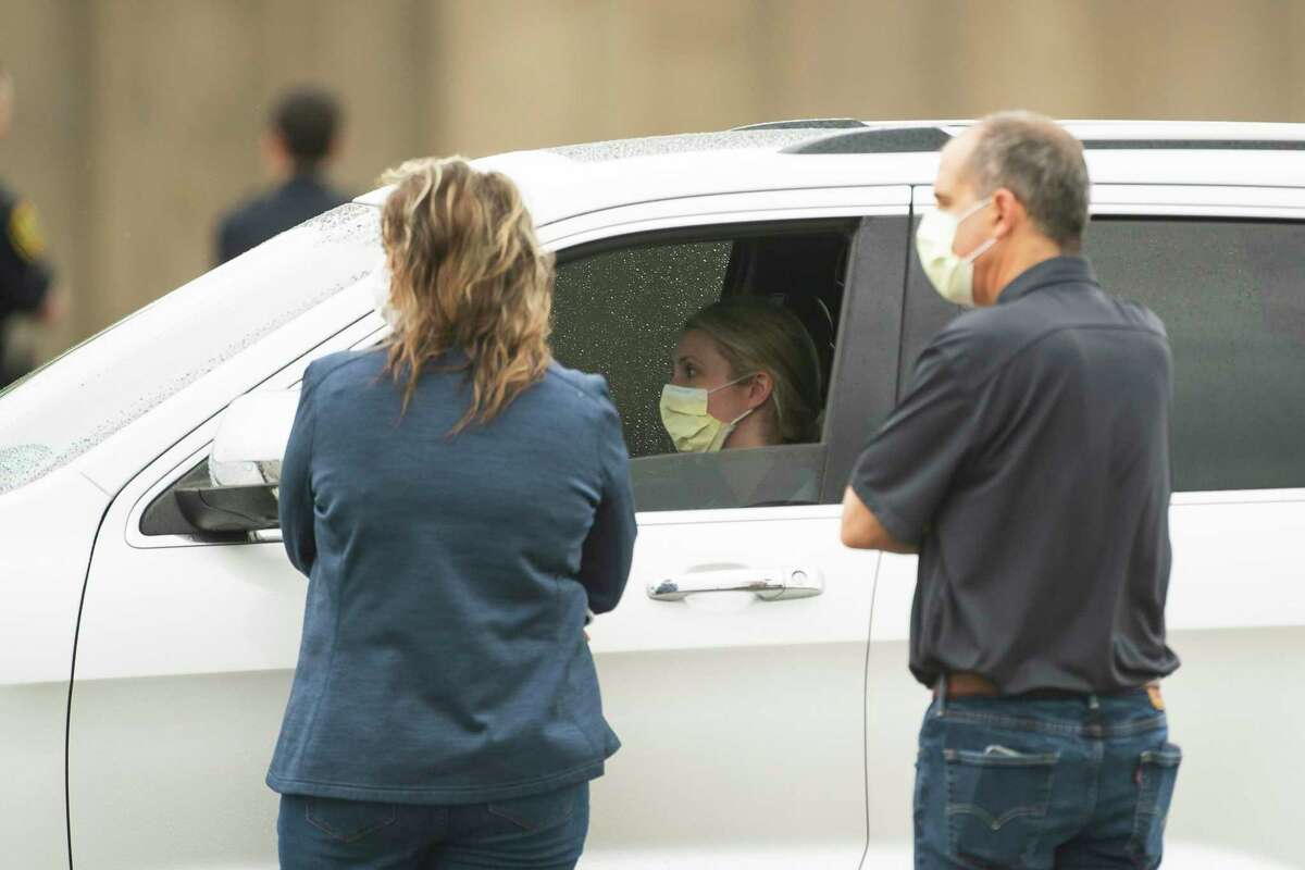 Healthcare professionals talk to drivers as they wait in line at the drive-thru testing center that opened to health care professionals and first responders, Friday, March 20, 2020, at Butler Stadium in southwest Houston. Everyone who arrived was already pre-screened and had to provide a unique ID number at the entrance to gain access. The city says the location will open to the broader public in the future.