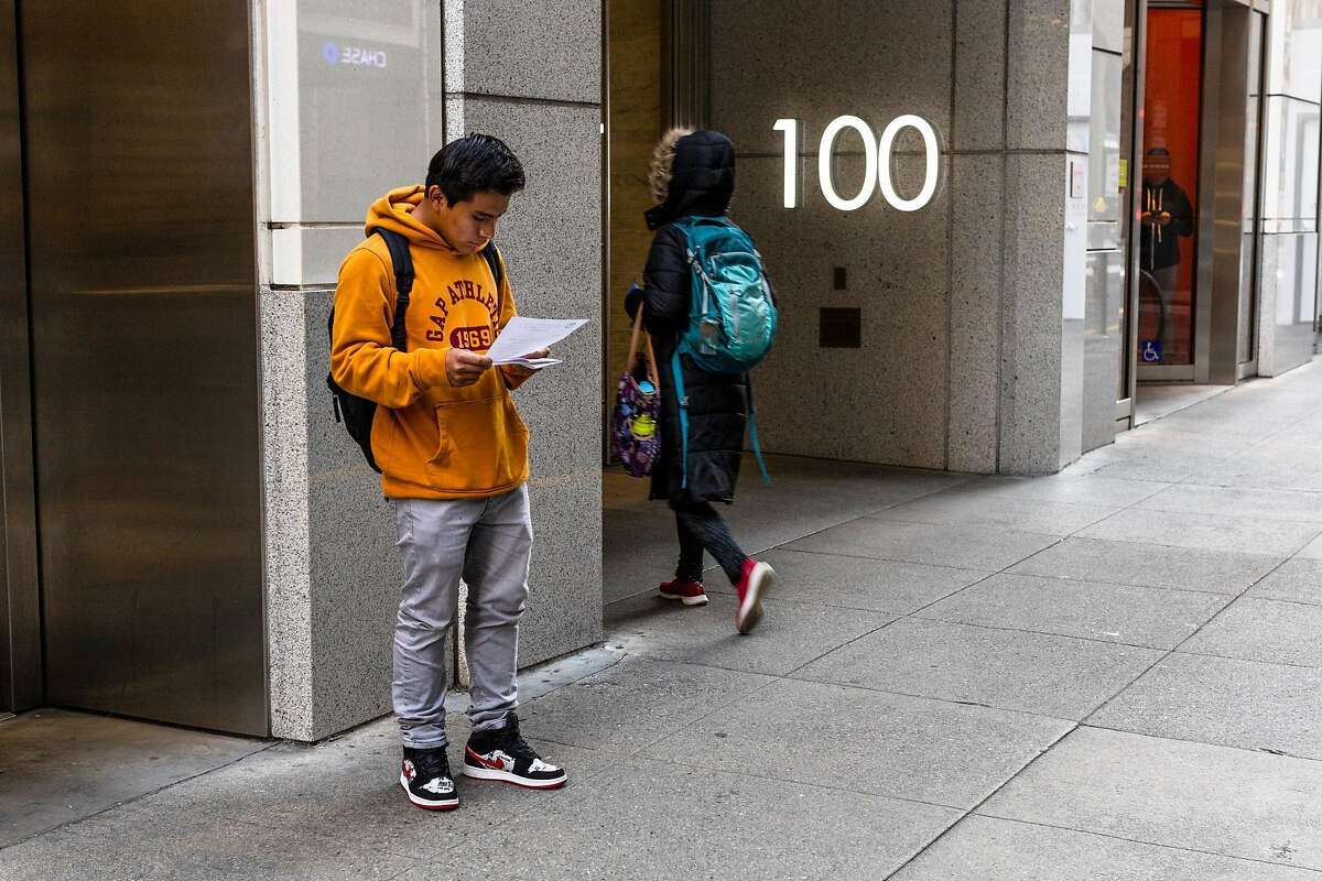 Ezequil Lopez reads an information sheet outside San Francisco Immigration Court on Friday, March 20, 2020, in San Francisco, Calif. Ezequil�s hearing was cancelled.