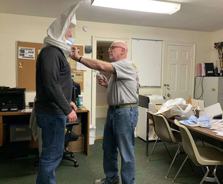 John Miscioscia, president of Wilton Volunteer Ambulance Corps, fits an N95 mask on WVAC member Kevin Kelly. Photo: Contributed Photo