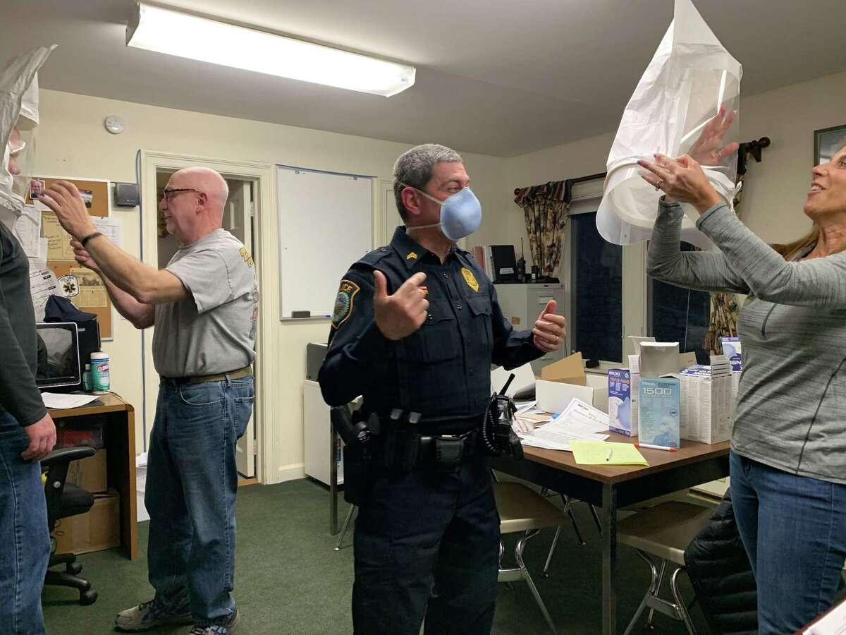 Diane McDermott, Wilton Volunteer Ambulance Corps member and EMT, does an N95 mask fitting for Sgt. Arnault Baker of the Wilton Police Department.