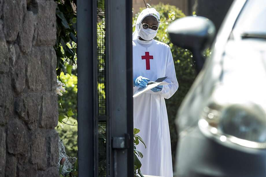 A nun wearing a mask and gloves stands at the Istituto Figlie di San Camillo (Institute of Daughters of St. Camillo) in Grottaferrata, near Rome, Friday, March 20, 2020. Outbreaks of the coronavirus have stricken two convents in the Rome area. Rome daily Il Messaggero quoted the Lazio region's health commissioner on Friday as saying 59 nuns at the Institute of Daughters of St. Camillo in the hill town of Grottaferrata have tested positive for COVID-19. For most people, the new coronavirus causes only mild or moderate symptoms. For some it can cause more severe illness. (Roberto Monaldo/LaPresse via AP) Photo: Roberto Monaldo / Associated Press