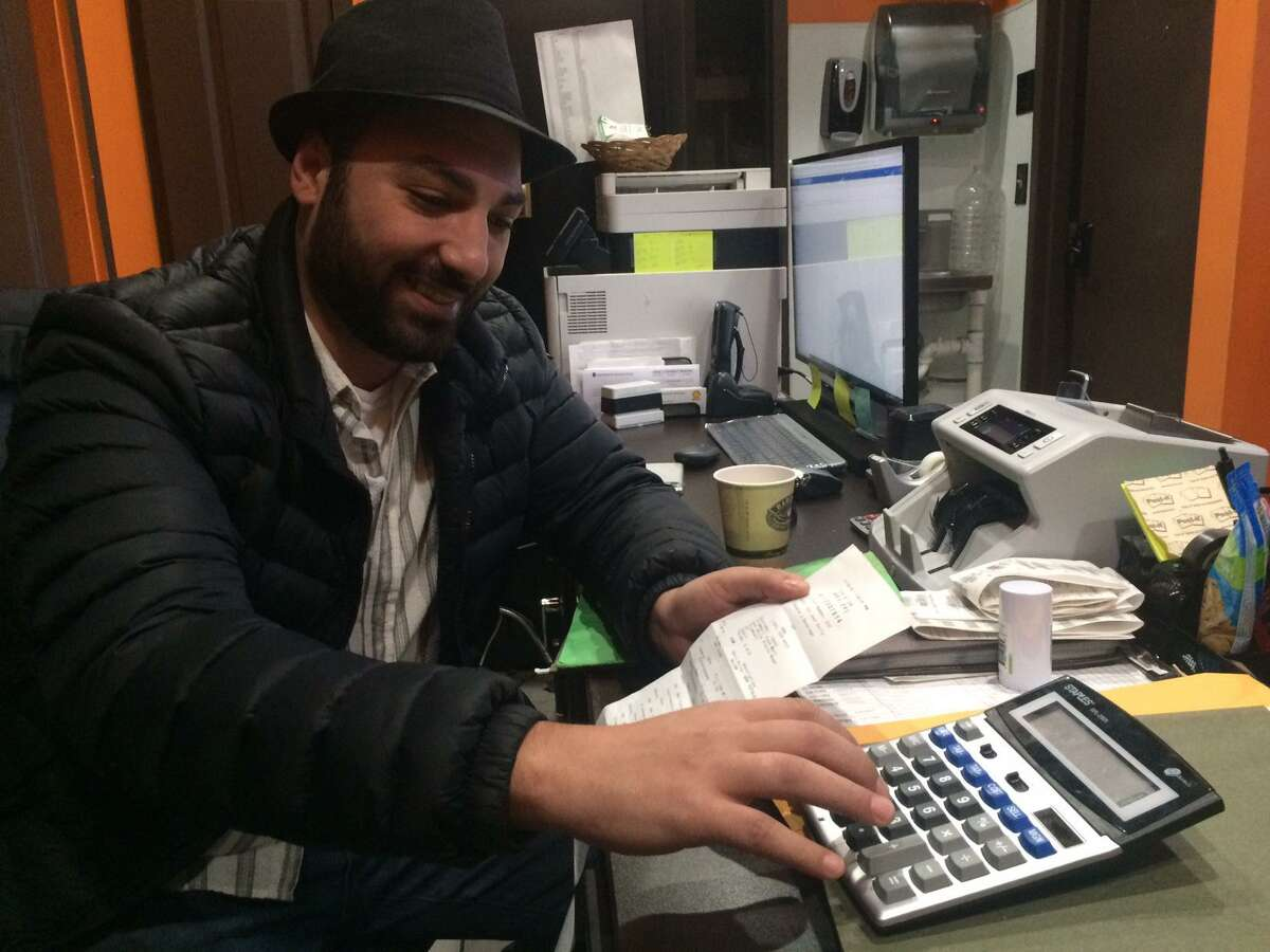Trumbull Food Mart owner Fadi Znbarakji calculates his profit on cases of water that he bought for more than $8 each.