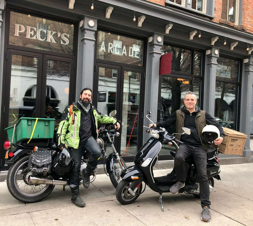 The delivery team for Clark House Hospitality of Troy includes server Kristoph DiMaria, left, and owner Vic Christopher. The company's businesses with products available for takeout and delivery are Little Pecks cafe, Peck's Arcade restaurant, Lucas Confectionery wine bar, The Bradley bar and the retail shop 22 2nd St. Wine Co.