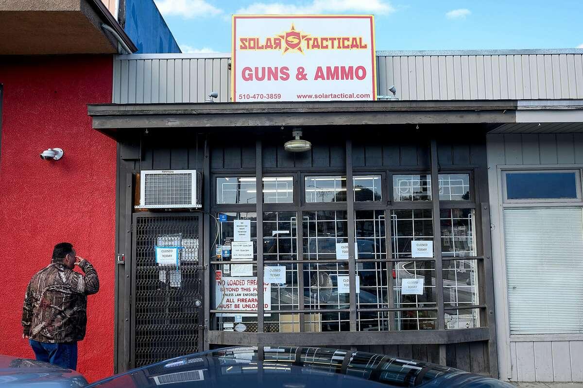 Solar Tactical customer Delfino Vasquez looks at the closed gun store on Friday, March 20, 2020, in Castro Valley, Calif. Store owner Mike Addis closed Friday after initially resisting coronavirus shelter-in-place orders shuttering non-essential businesses.