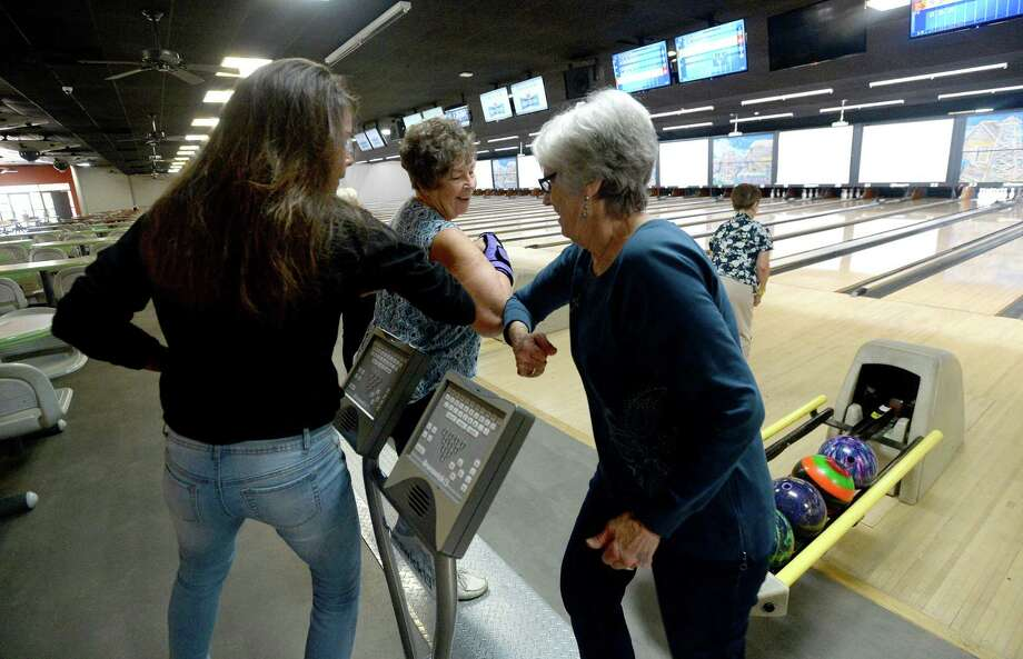 League members celebrate a strike with a group elbow bump as the Queen Tumblers League gather at the Max Bowl in Port Arthur for their usual Wednesday morning league games. Photo taken Wednesday, March 18, 2020 Kim Brent/The Enterprise Photo: Kim Brent / The Enterprise / BEN