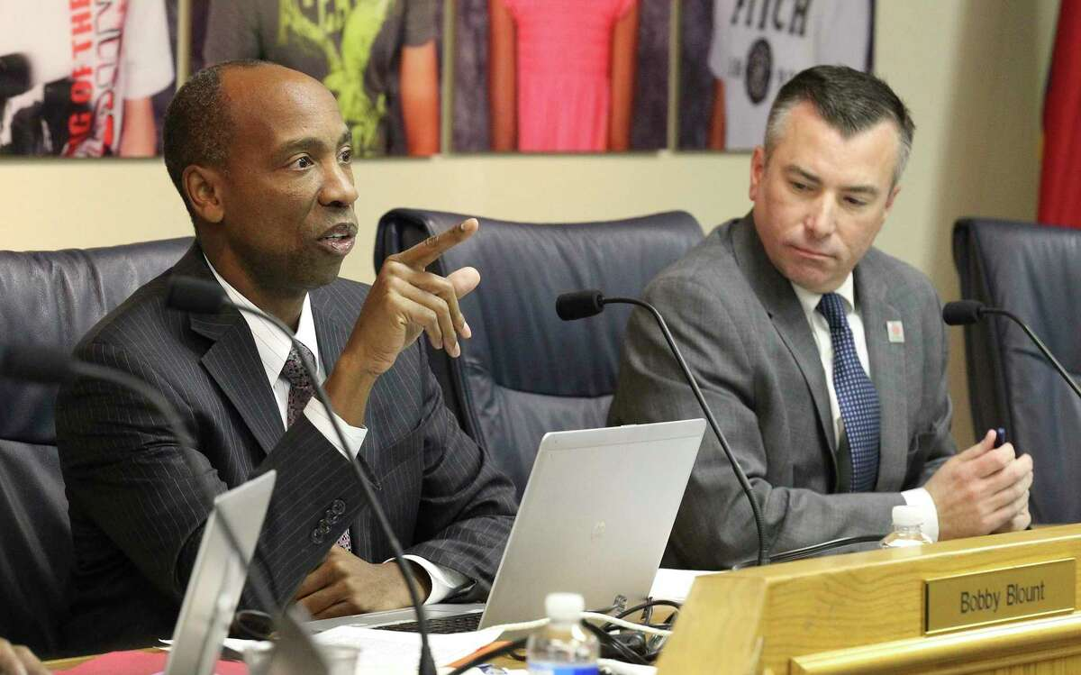 Northside ISD Board trustee Robert Blount Jr. (left), who was then the board president, and Superintendent Brian Woods address the public during a meeting in 2013. (Kin Man Hui/San Antonio Express-News)