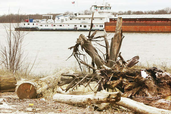 As if the area didn't have enough to deal with during the COVID-19 pandemic, flooding is now expected on the Mississippi and Illinois Rivers next week. On Friday, a towboat pushing upstream passes piles of river debris - including logs and stumps - left from last year's historic flooding.
