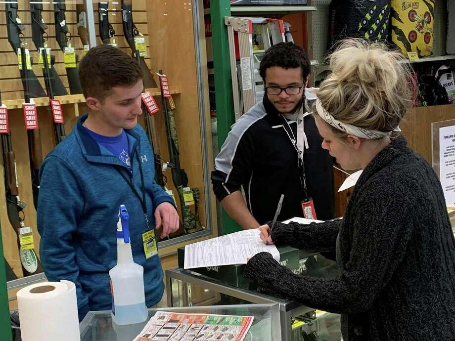 Dunham's Sports managers Ty Fulco and Miles Davenport helpMorgan Sian purchase a gun on March 18, 2020. (Mitchell Kukulka/Mitchell.Kukulka@mdn.net)