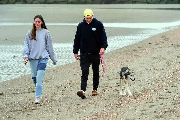 Owen Mulvaney and frend Ella Brassinga, both of Ridgefield, walk along the beach with Jade at Penfield Beach in Fairfield, Conn., on Friday Mar. 20, 2020.