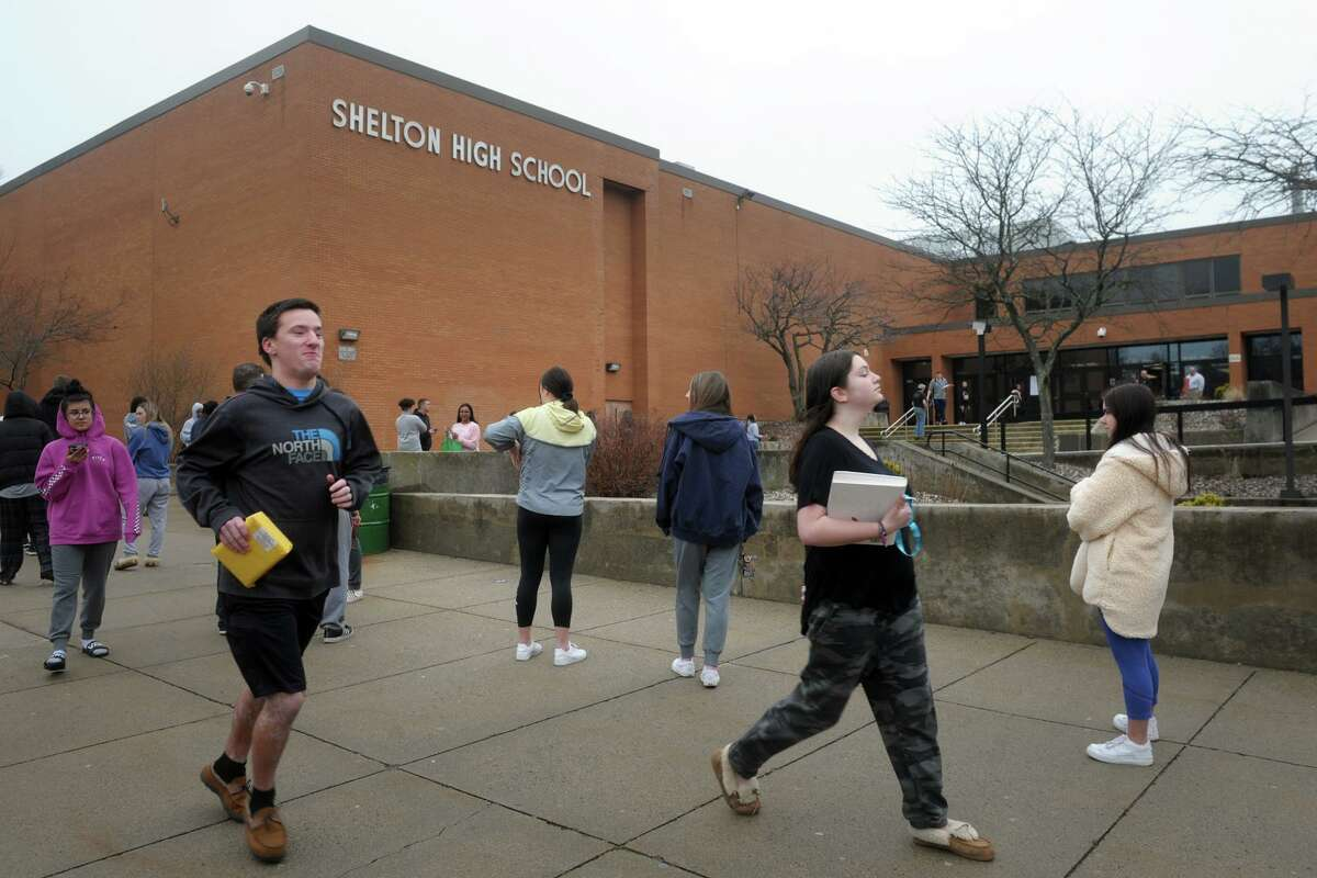 Students and parents line up outside Shelton High School in Shelton on March 20. Students were allowed into the school to pick up all their personal belongings as well as books, computer gear and various supplies needed for distance learning as schools closed due to the coronavirus pandemic.