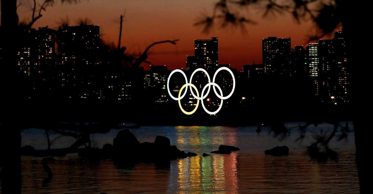The sun sets behind the Olympic rings installation at Odaiba Marine Park on March 18, 2020 in Tokyo, Japan. (Photo by Clive Rose/Getty Images)