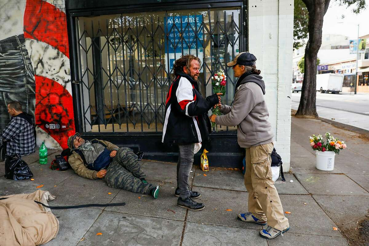 Paola Bottone (right) gives a homeless man (declined name) free flowers after a friend of Bottone�s who owned a flower shop had to close on Haight Street on Tuesday, March 17, 2020 in San Francisco, California. The city is ordered to shelter in place due to the coronavirus.