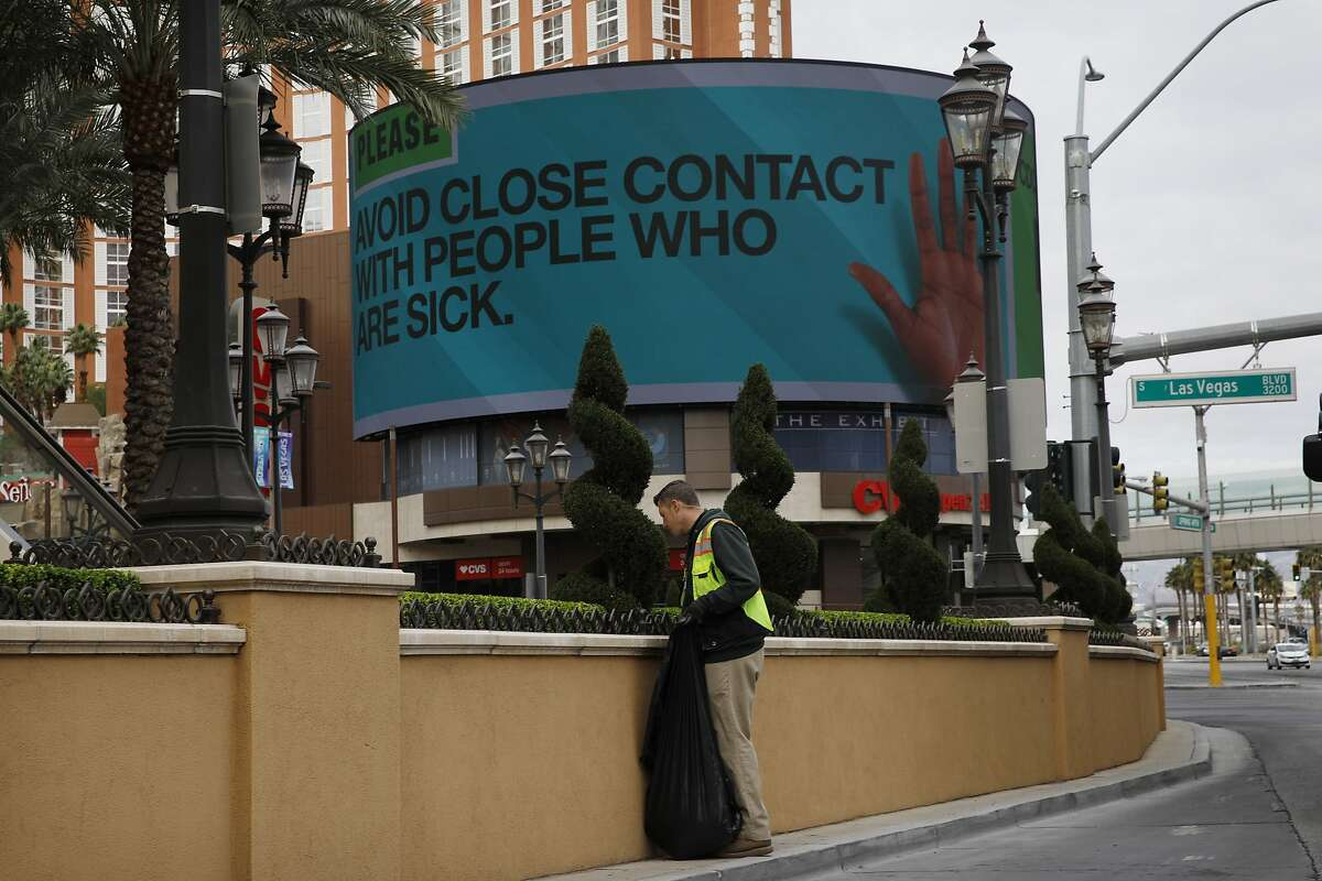 A worker cleans up in front of the Palazzo hotel as a sign warns to avoid contact with sick people after casinos have been ordered to shut down along the Las Vegas Strip due to the coronavirus Wednesday, March 18, 2020, in Las Vegas. For most people, the new coronavirus causes only mild or moderate symptoms, such as fever and cough. For some, especially older adults and people with existing health problems, it can cause more severe illness, including pneumonia. (AP Photo/John Locher)